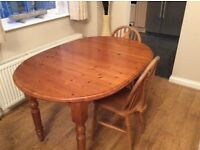 Antique pine finish extendable oval dining table and 4 chairs.