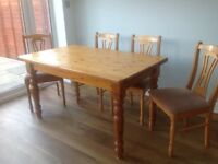 Farmhouse kitchen pine dining table and four chairs.