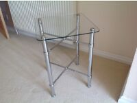 Beautifu pair of solid chrome and glass bed side tables.
