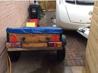 Car trailer with axle and leaf springs, lights, cover.
