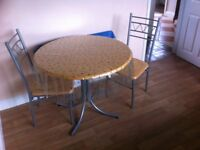 Round dining table complete with four chairs