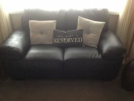 two seater settee in new condition hardly ever sat on , black leather look