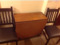 Solid wood drop leaf table and four sturdy wooden chairs. NOW GONE