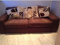 Dark brown sofa with scatter cushions. 1 tiny hole on each of the base cushions.