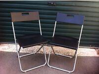 IKEA pair of black plastic folding chairs