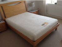 As new 4ft 6 ins double bed in light oak plus mattress and two matching bed side cabinets