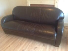 A dark brown leather bed settee