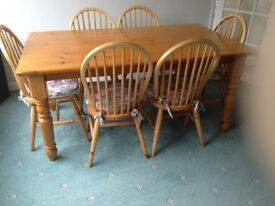 Large pine dining table and 6 chairs complete with cushions.