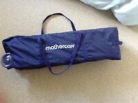 Mothercare navy travel cot with separate mattress.