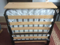 Like new, self folding single guest bed, with mattress cover and bed clothes