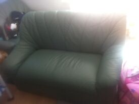 2 Green leather sofas great condition!! Free glass coffee table