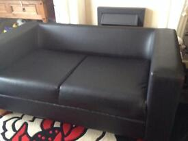 Faux leather two seater sofa in very good condition.