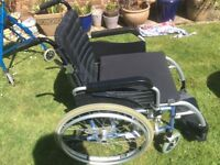 Wheel chair , self propelled by excel vanos , blue and silver, with seat cushion.
