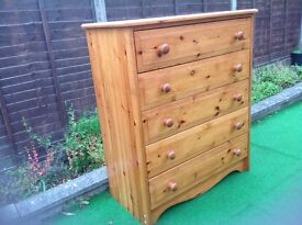 A tall pine chest of 5 drawers on plinth,