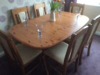 Extendable pine dining room table and six chairs .