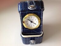 Small travel alarm clock in case with room for storing a few items