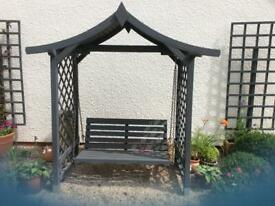Wooden garden arbor with swing seat