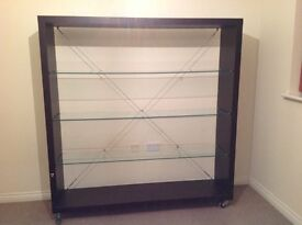 Available today!! Beautiful dark wood shelving unit on castors with glass shelves