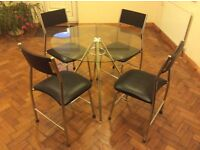 90cm glass topped table ,chrome metal underframe , four matching chairs with black upholstery .