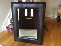 Broad framed brown leather effect mirror.