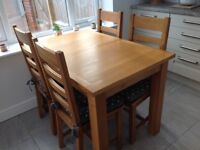 Solid oak extending dinning table and four chairs