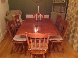 extendable dining room table and six chairs with cushions.