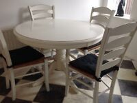 White kitchen table with four wicker topped chairs
