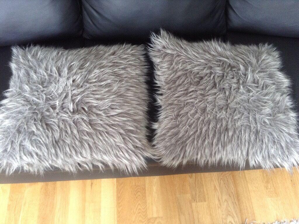 Two fluffy grey cushions