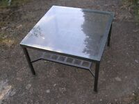 COFFEE TABLE 27 INCHES SQUARE, 17 INCHES HIGH, GLASS TOP, WITH MAGAZINE SHELF.