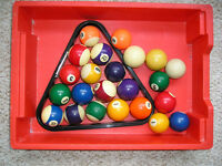 A NUMBER OF POOL BALLS AND TRIANGLE.