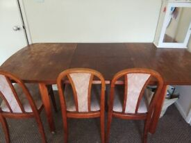 a wooden dining table with 4 chairs