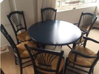 Dining table with six whicker chairs (two with arm rests) by French brand Bree Societe.