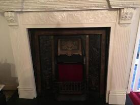 Beautiful cast iron fire place with slate hearth and carved wood surround