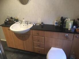 Bathroom Vanity Unit with sink, toilet and storage. Black granite top.