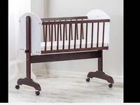 White and brown rocking baby crib on wheels