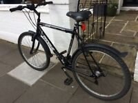 Adult bicycle in full working order with lights and mudguards.