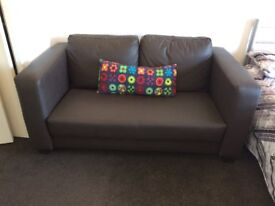 Brown Faux Leather two seater sofa.