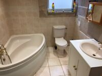 Corner bath, toilet and sink with unit, Taps are brass effect, coral in colour