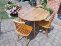 A DINETTE VINTAGE PINE TABLE WITH FOLDING SIDES AND 4 SPINDLE BACKED CHAIRS