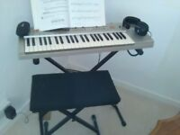 Basic first level key board with stand, stall, ear phones and music sheets