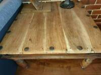 Coffee table with metal ends and wheels.