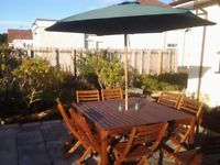 Large garden table and 8 chairs ,parasol and base