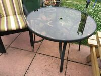 Glass top wrought iron table , complete with 4 chairs and cushions