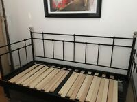 Black framed Ikea day bed which pulls out into a double