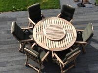 Round 1.5m wooden garden table with lazy susan and 6 reclining chairs with cushions