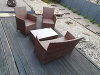 Rattan two seater, two chairs and a table
