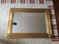 Gold framed rectangular mirror.