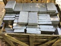 Two crates of assorted black limestone driveway blocks