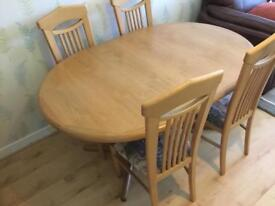 Extendable solid wood dining table and 6 chairs, in good condition.