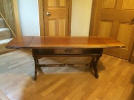 Traditional hard wood coffee table in good condition. Two extending leaves and one drawer.